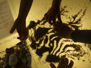 mani sabbia pietre luce